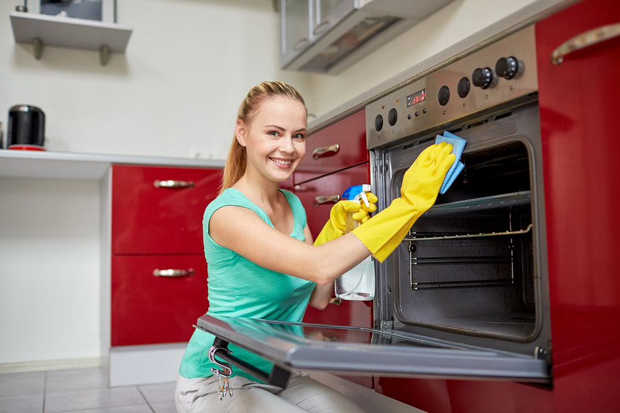 cleaner doing oven cleaning